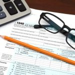 Papel e óculos sobre a mesa com uma calculador ao lado