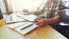 Mulher sentada em frente a um laptop segurando caneca em uma mão e tablet na outra