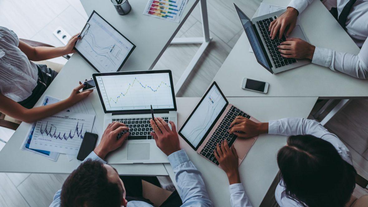 4 pessoas na mesa com laptop trabalhando
