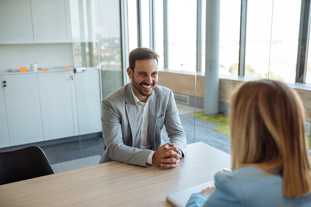 Homem sorrindo confiante em entrevista com uma mulher