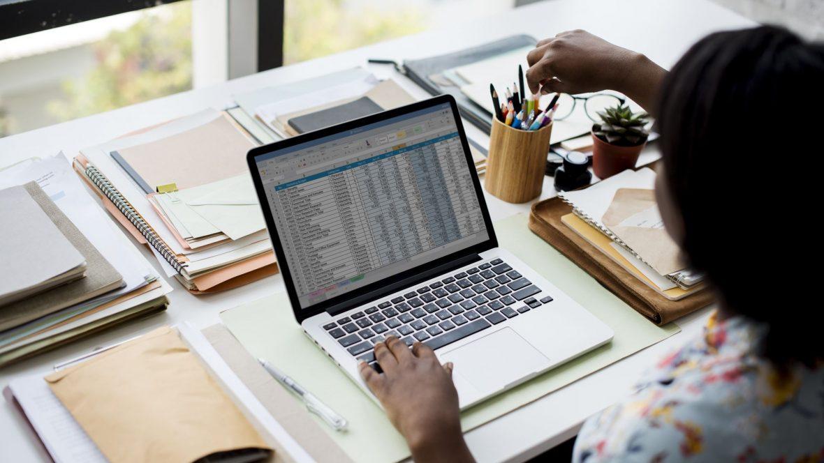 Mulher pegando caneta e usando laptop